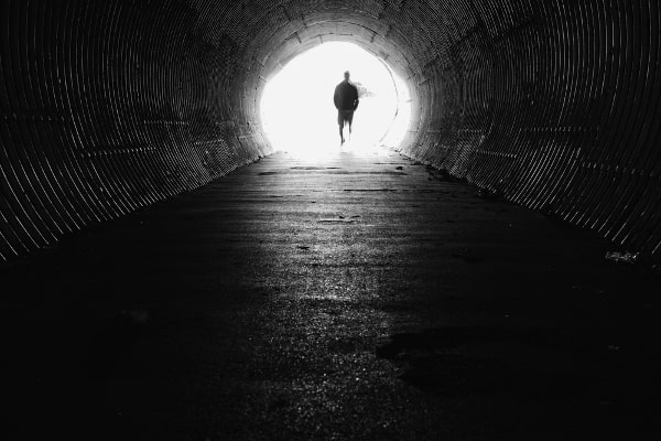 Person Walking Towards Light at End of Dark Tunnel