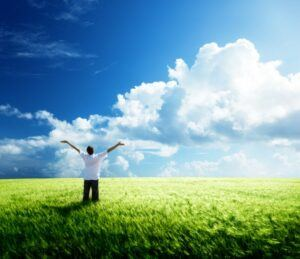 Man in Field with Arms Outstretched Looking at Sky